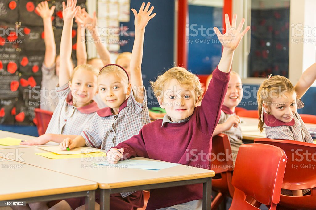 Happy School Children Answering a Question in the Classroom stock photo