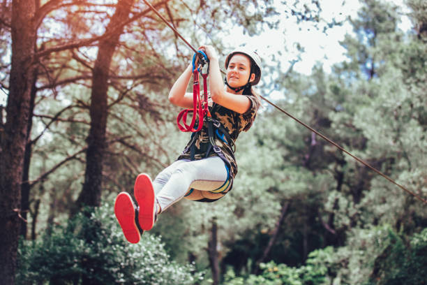 Happy school girl enjoying activity in a climbing adventure park on a summer day Happy school girl enjoying activity in a climbing adventure park on a summer day zip line stock pictures, royalty-free photos & images