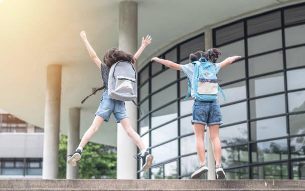 Glückliche Mädchen Schulkinder (Grundschüler) Rückansicht mit Rucksäcken springen, um gonna Klasse am ersten Tag zurück zu Schule Bildungskonzept feiern – Foto