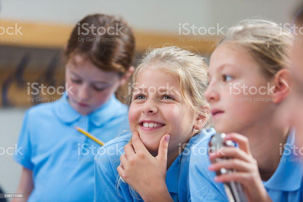 Happy School Girl Listening in Class stock photo