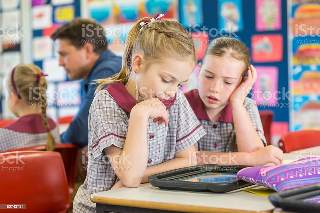 Happy School Girls Using Tablet Computers In The Classroom stock photo