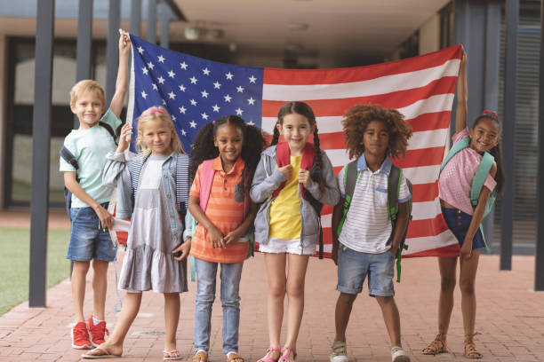Happy school students standing in corridor while holding american flag stock photo