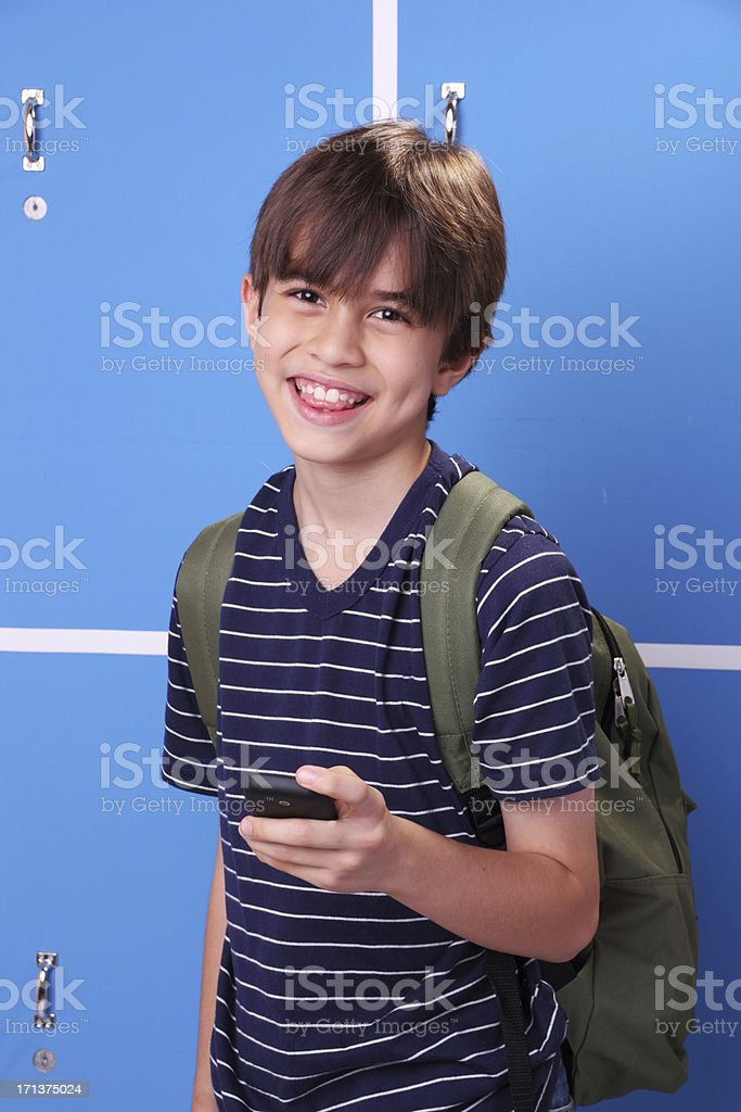 Happy schoolboy with his cel phone royalty-free stock photo