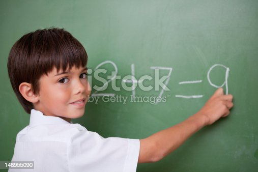 istock Happy schoolboy writing an addition 148955090