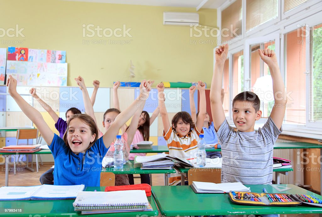Happy schoolchildren raising hands upwards. royalty-free stock photo