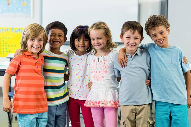Happy schoolchildren standing in classroom stock photo