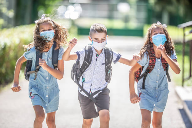 Happy schoolchildren with face masks run from the joy of returning to school during the Covid-19 quarantine. stock photo
