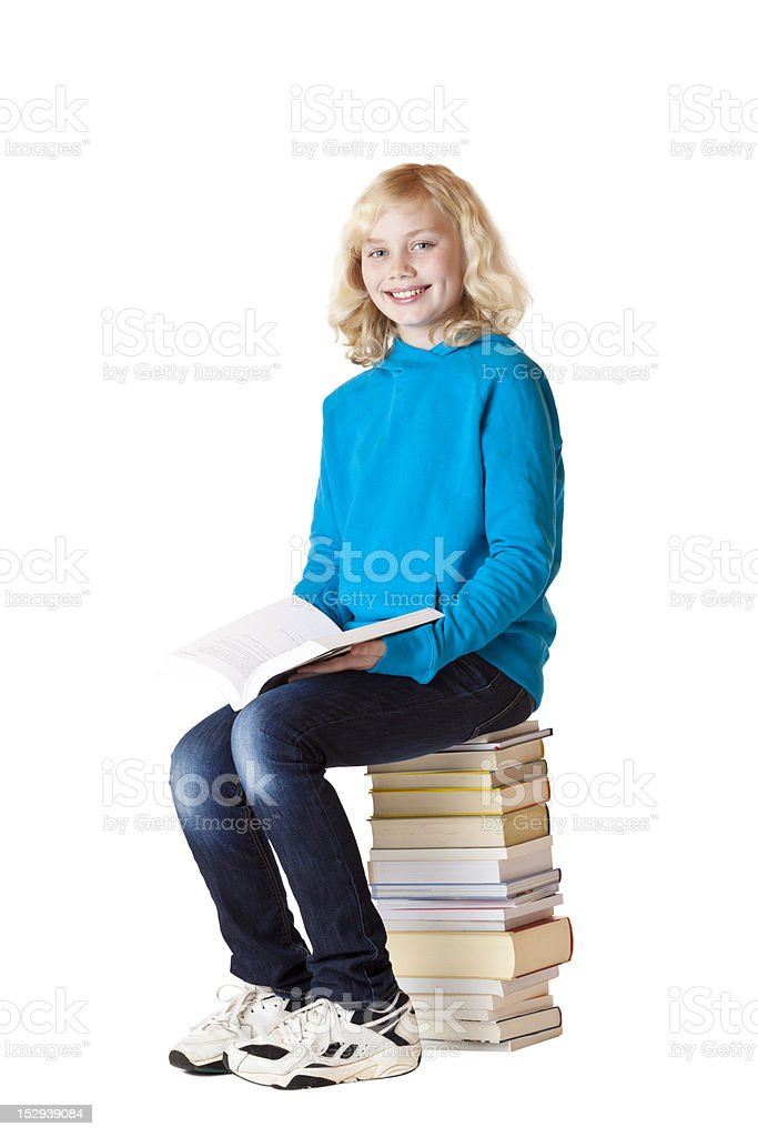 Happy schoolgirl holding book and sitting on school books royalty-free stock photo