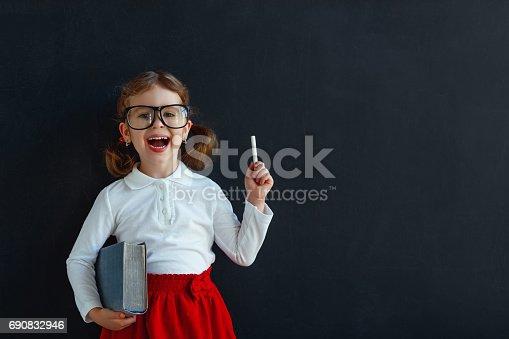 istock Happy schoolgirl preschool girl with book near school blackboard 690832946