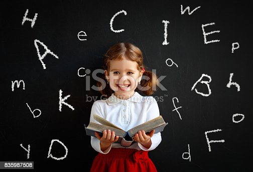 istock Happy schoolgirl preschool girl with book near school blackboard 835987508