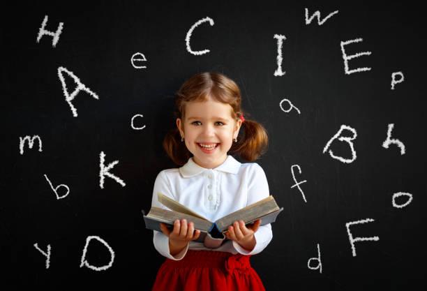 glücklich schulmädchen vorschul mädchen mit buch in der nähe von schultafel - schöne englische wörter stock-fotos und bilder