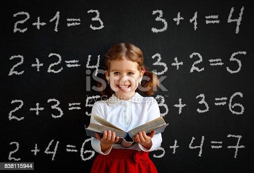 istock Happy schoolgirl preschool girl with book near school blackboard 838115944