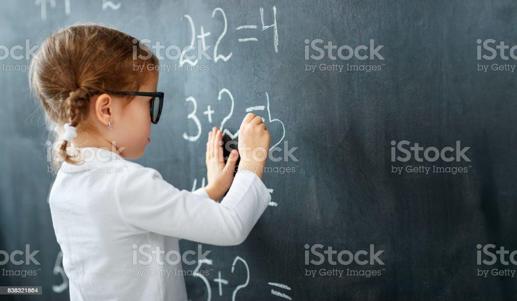 Happy schoolgirl preschool girl with book near school blackboard - Royalty-free Baby - Human Age Stock Photo