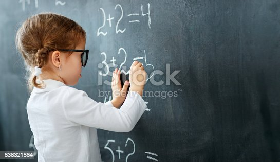 istock Happy schoolgirl preschool girl with book near school blackboard 838321864