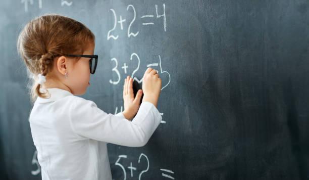 Fille d'âge préscolaire heureuse écolière avec livre près de tableau noir école - Photo