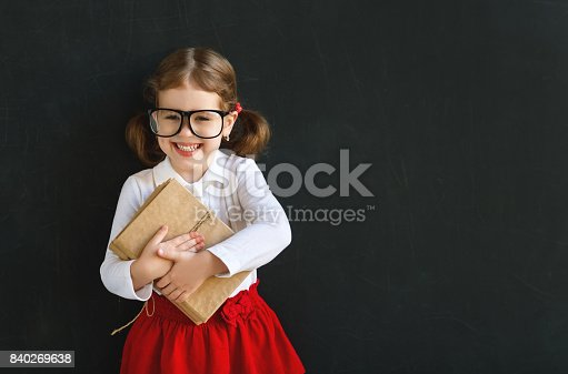 istock Happy schoolgirl preschool girl with book near school blackboard 840269638