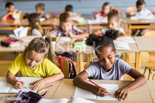 Happy Asian and African American elementary students writing in their notebooks while having a class at school. Their classmates are in the background.
