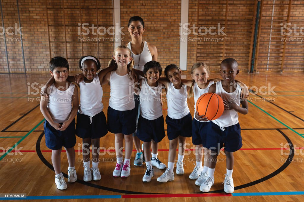 Front view of happy schoolkids and female coach looking at camera at...