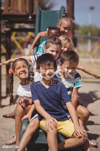 istock Happy schoolkids playing in playground 846441744