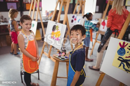 Portrait of happy schoolkids practicing drawing