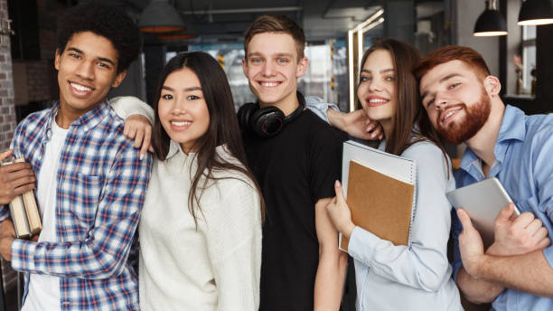 gelukkige klasgenoten die samen poseren, glimlachen om de camera - slagen school stockfoto's en -beelden