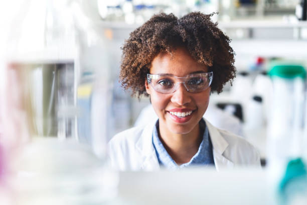 happy scientist wearing protective eyewear in lab - scientist imagens e fotografias de stock