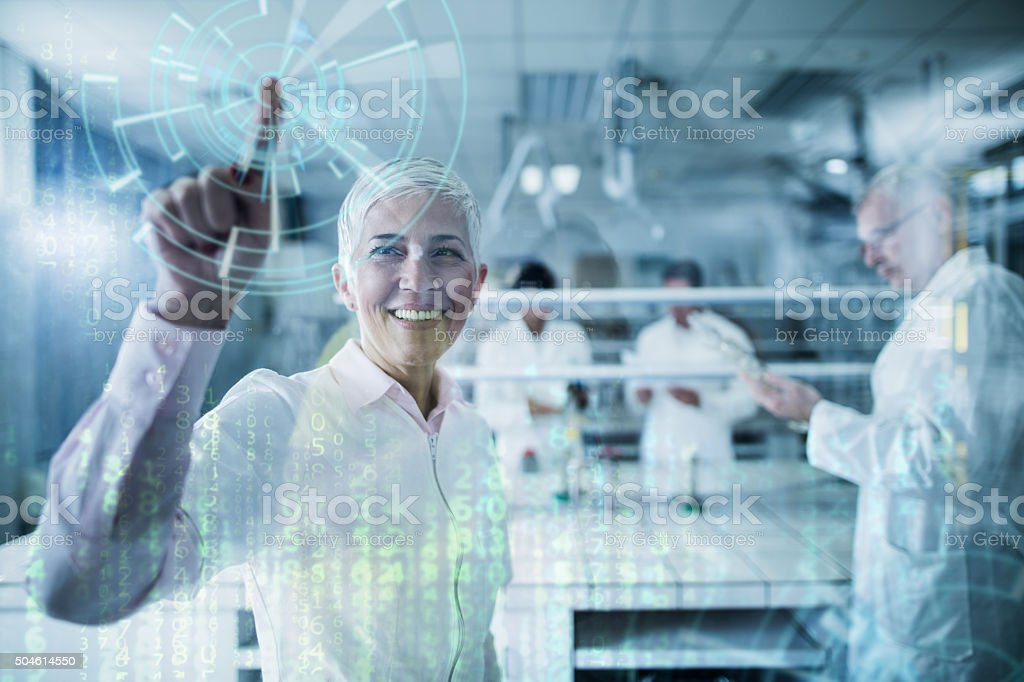 Happy scientist working on futuristic innovation on a touch screen. stock photo