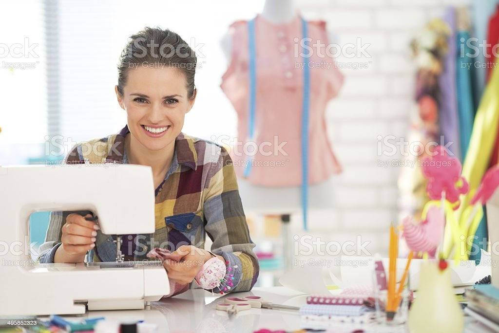 happy seamstress sewing in studio stock photo