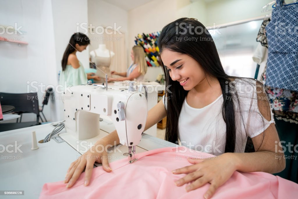 Happy seamstress sewing on a machine at an atelier stock photo