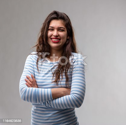 Happy self-assured young woman with folded arms standing looking at the camera with a vivacious warm friendly smile over a grey studio background