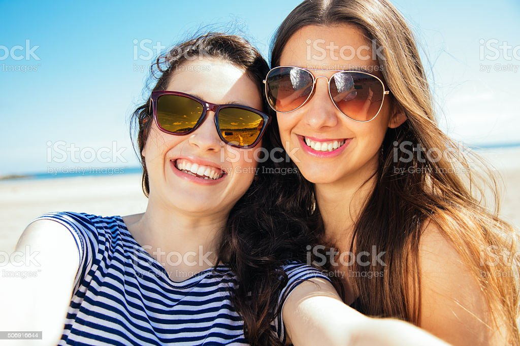 Happy selfie friends on the beach stock photo