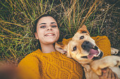 Happy dog and his favorite person taking selfie on camping in forest
