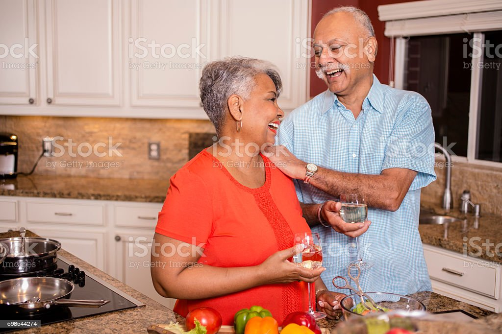 Happy senior adult couple cooking together in home kitchen. photo libre de droits