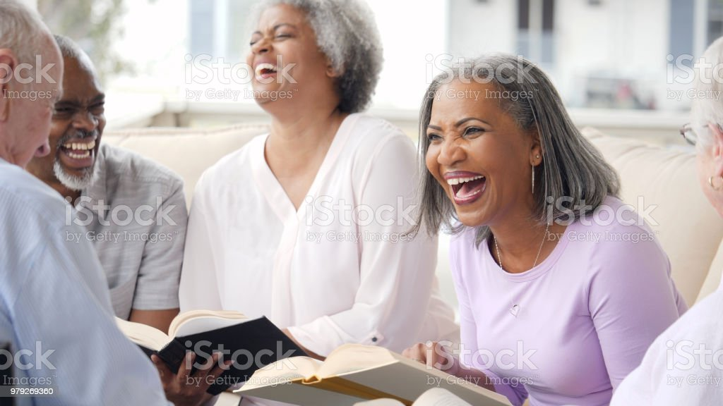 Happy senior adult laugh during book club meeting stock photo