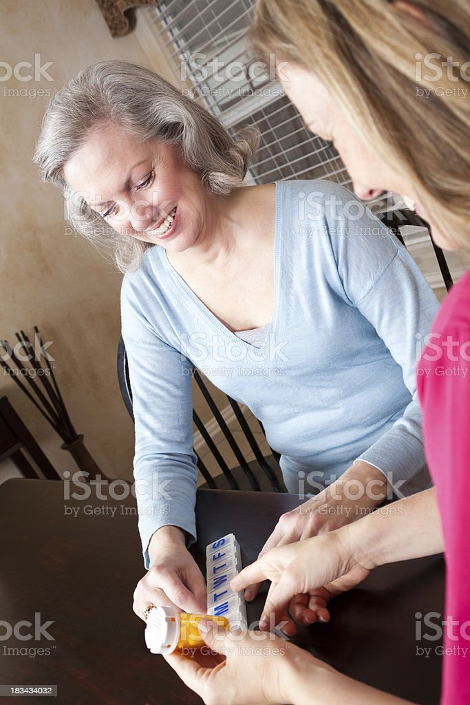 Happy Senior Adult Looking Over Medication With Healthcare Nurse royalty-free stock photo
