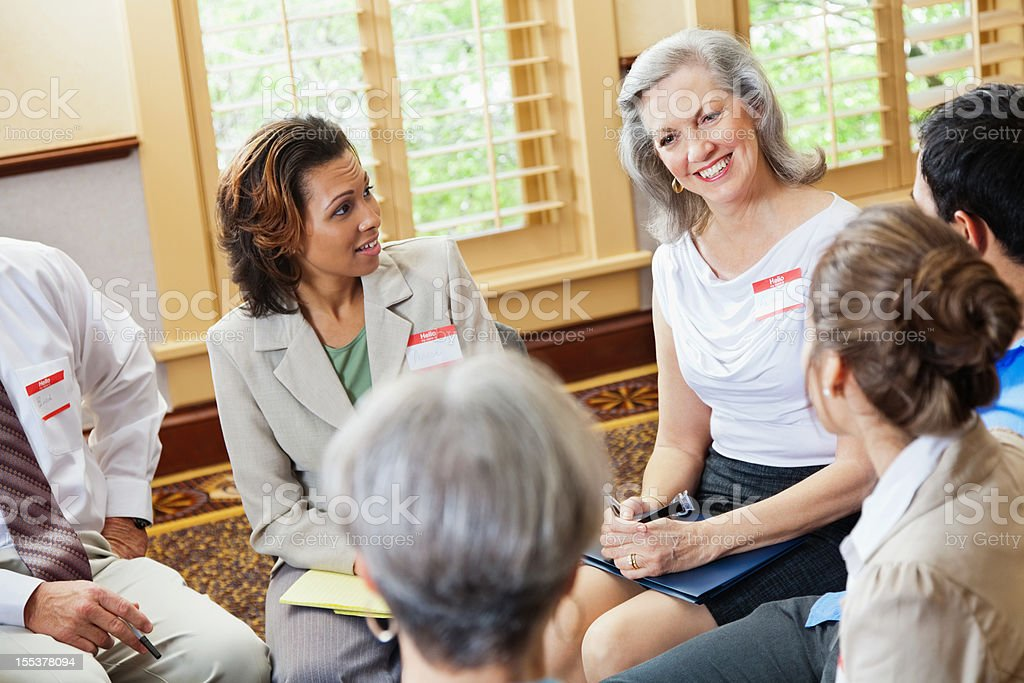 Happy senior adult woman talking in a group setting royalty-free stock photo