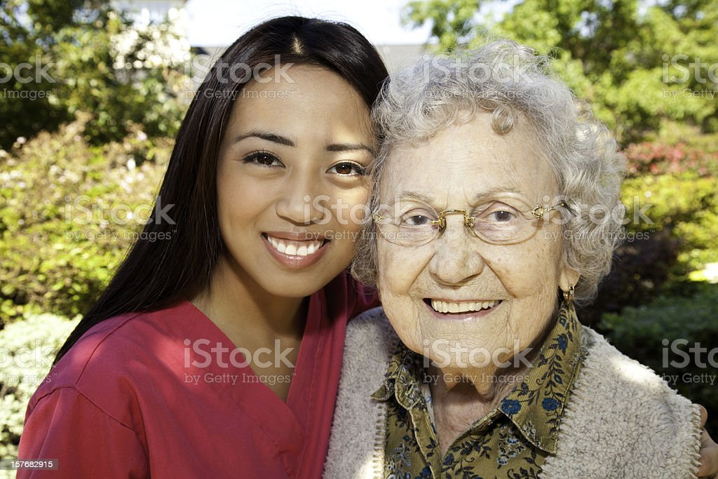 Happy Senior Adult Woman With Her Young Caretaker Nurse royalty-free stock photo