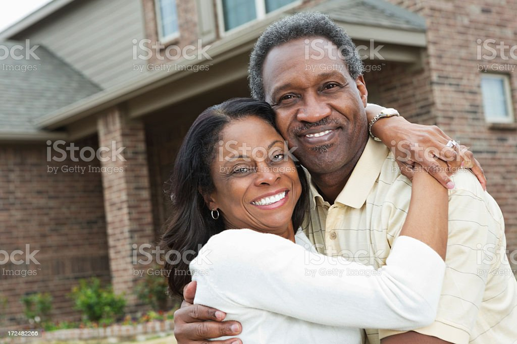 Happy senior African American couple standing outside home stock photo