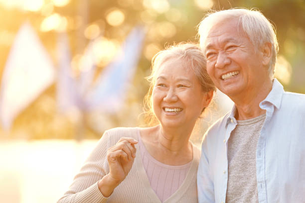 happy senior asian couple relaxing outdoors stock photo