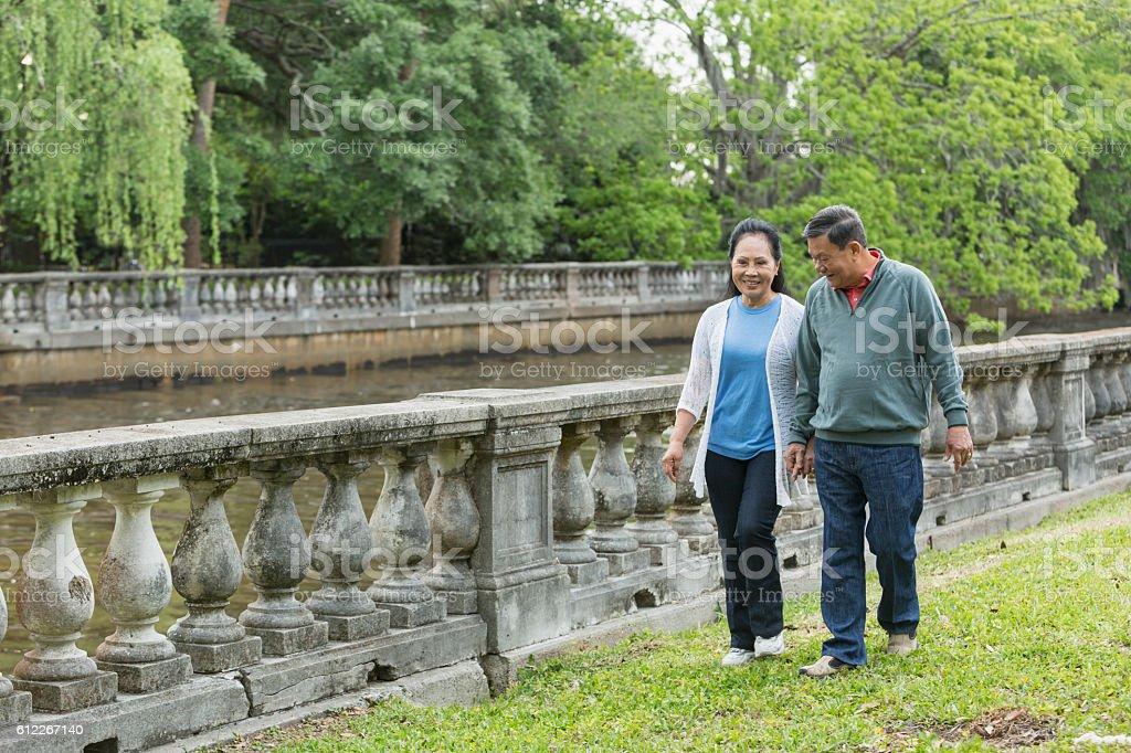 Happy senior Asian couple walking in park stock photo