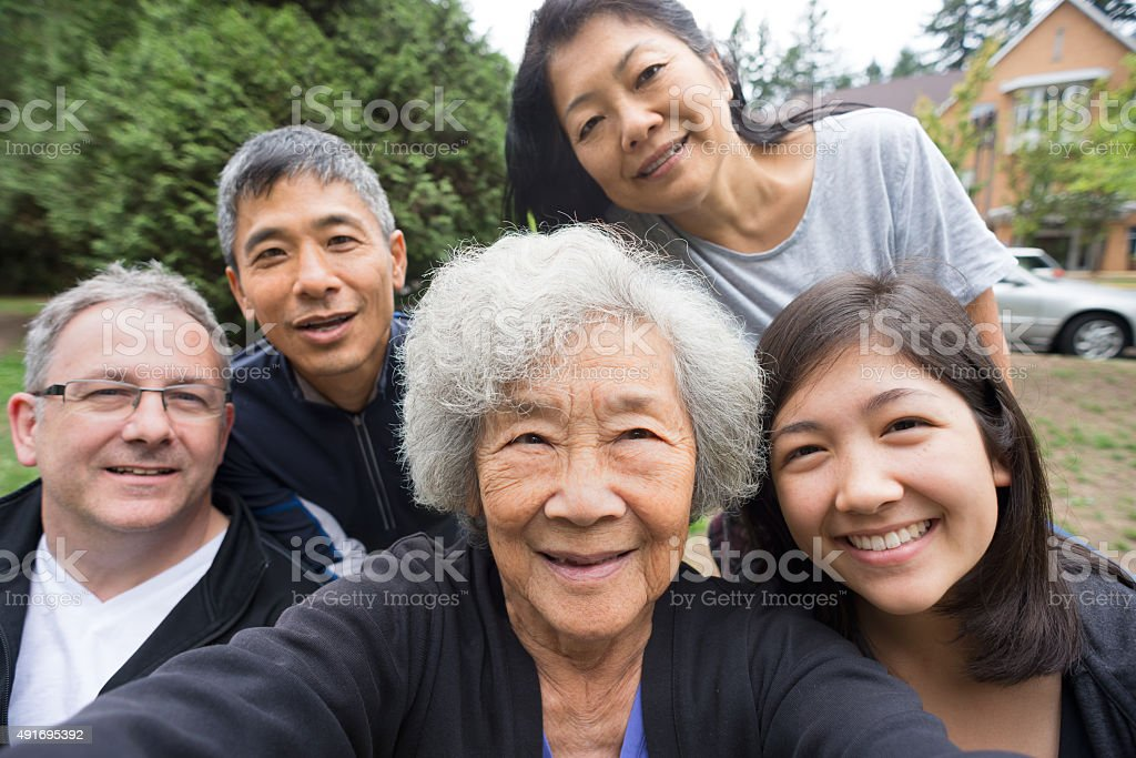 Happy Senior Asian Woman Taking Selfie with Family in Park stock photo
