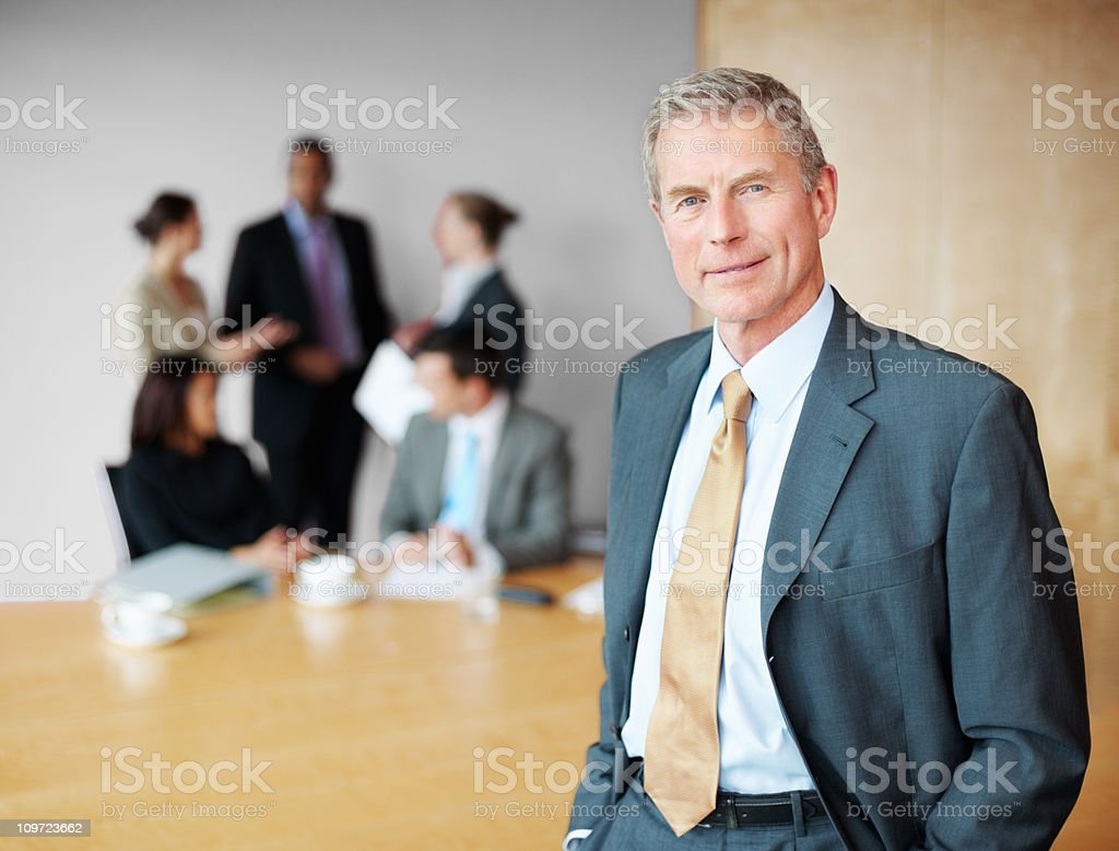 Happy senior business man with his blur team in background royalty-free stock photo