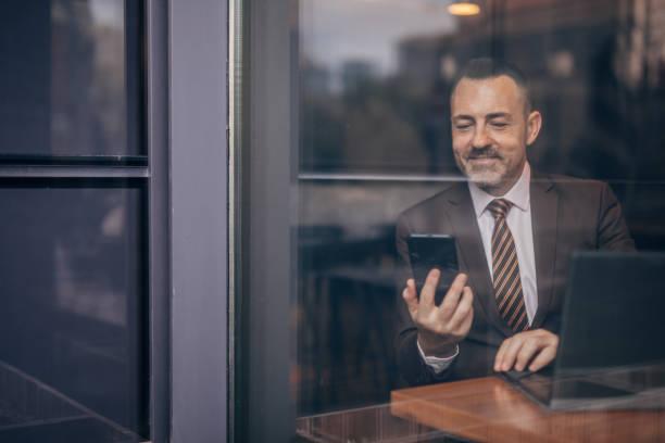 Happy senior businessman having a video call stock photo