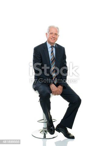 Happy senior businessman sitting on chair.