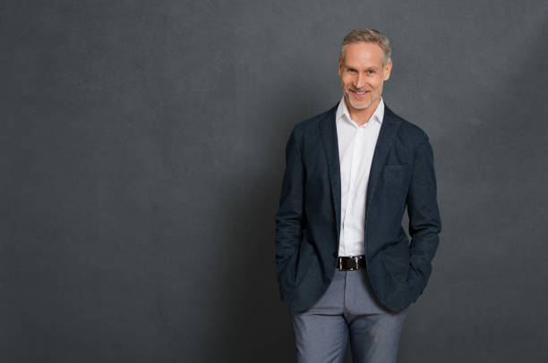 Happy senior businessman Happy senior businessman wearing suit standing over grey wall and looking at camera. Portrait of successful leader standing isolated gray background with copy space. Handsome mature man with fashion clothes. hands in pockets stock pictures, royalty-free photos & images