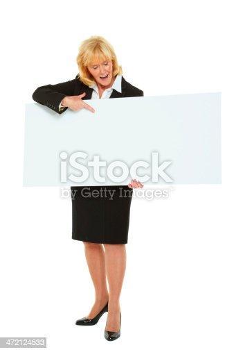 157609352 istock photo Happy senior businesswoman showing you blank billboard 472124533