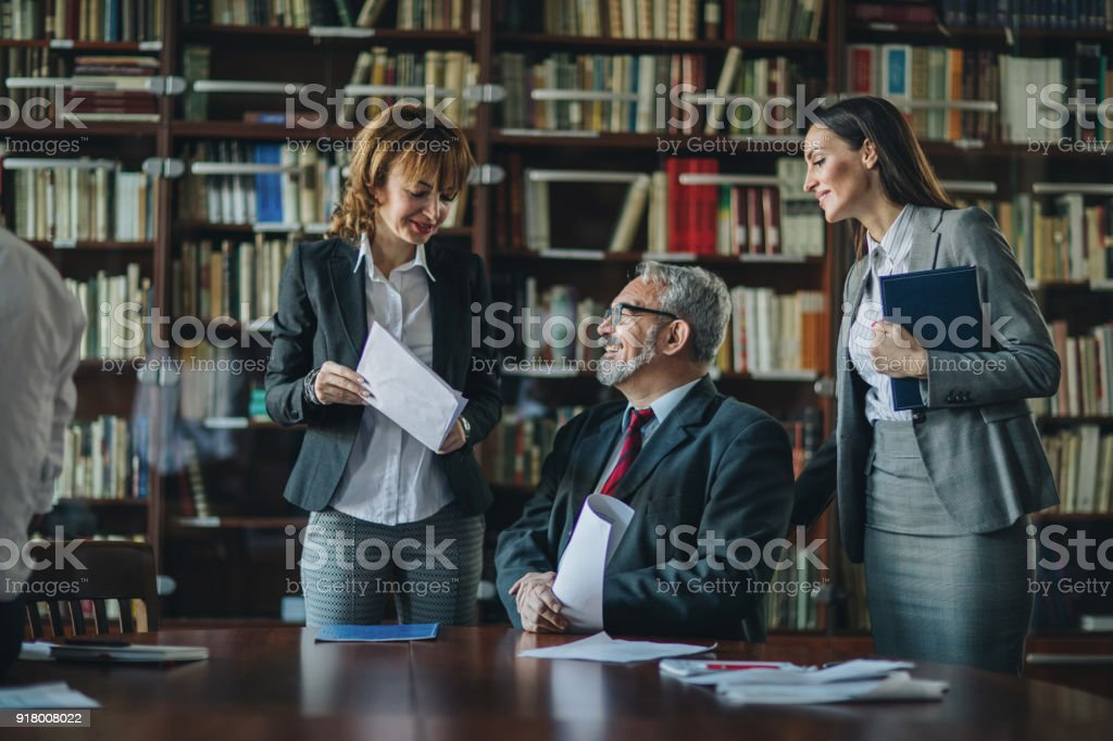 Happy senior CEO going through paperwork with two female colleagues. stock photo