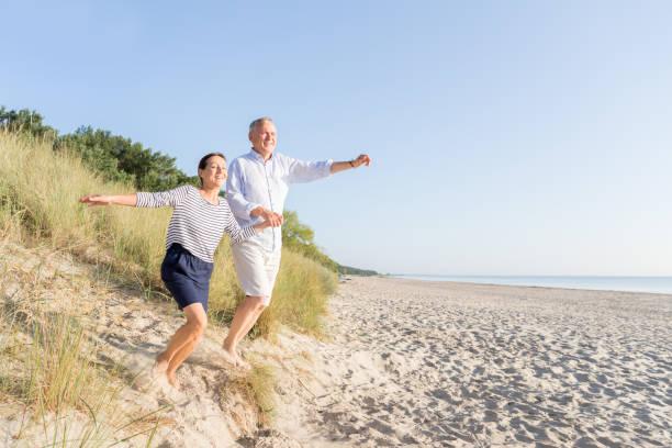 glückliches seniorenpaar am strand - wellness ostsee stock-fotos und bilder