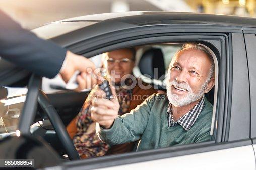Happy senior couple buying a car.