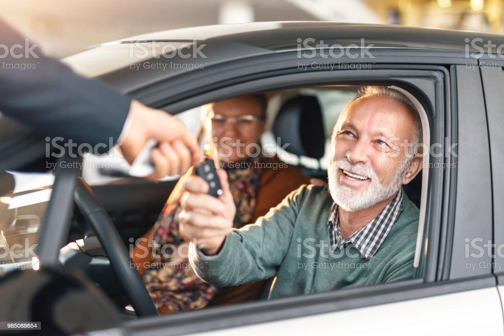 Happy senior couple buying a car. stock photo